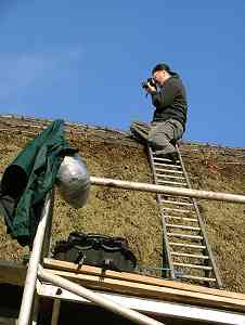 John records the thatch before starting work