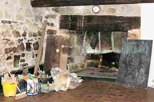 The East fireplace with tools and broom piled nearby
